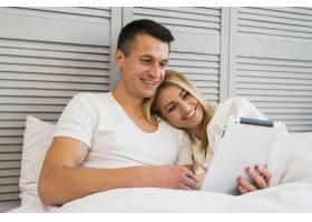 年轻的幸福夫妇在床上用毯子盖着平板电脑_3544787