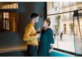 年轻的微笑的男人和快乐的女人靠窗拿着酒杯_3597257