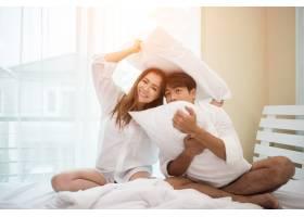 幸福的年轻夫妇在床上玩得很开心_3398366