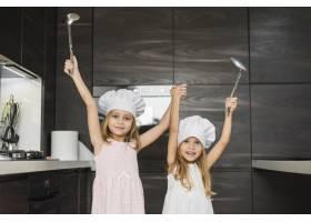 微笑的兄弟姐妹在厨房里举起手拿着勺子_3764696