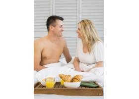 微笑的夫妇坐在床上靠近早餐桌上的食物_3544827