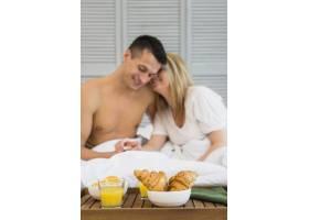 微笑的夫妇手牵手躺在床上早餐桌上的食物_3544831