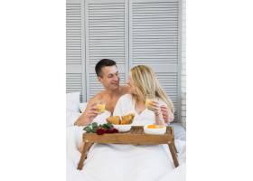 微笑的女人和男人戴着眼镜躺在床上早餐桌_3544846