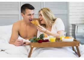 微笑的女人在早餐桌上食物旁边的床上给男人_3544839