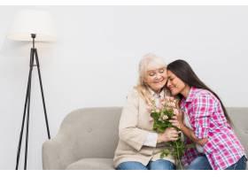 微笑的成年女儿抱着幸福的年长母亲手持花束_3764629