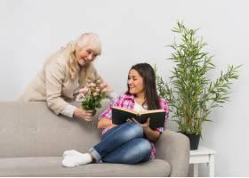 微笑的成熟女子给女儿送玫瑰花在家看书_3764557