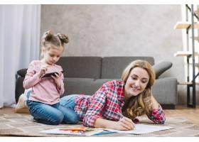 微笑的母亲用手机和女儿一起画书_3817189