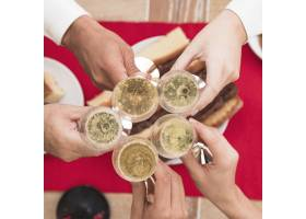 人们在喜庆的餐桌上叮当作响香槟酒杯_3329640