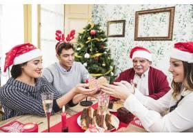 人们在圣诞餐桌上互相赠送礼物_3329729