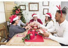 人们在节日餐桌上互相赠送礼盒_3329724