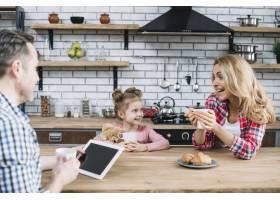 兴高采烈的父母和女儿在厨房里享用早餐_3831152