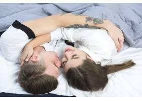 可爱的情侣在白色的床上拥抱_3579909