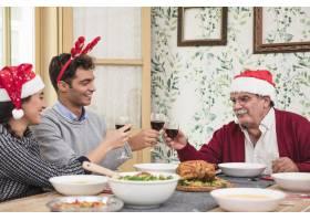 圣诞老人戴着帽子的人在圣诞桌上碰杯叮当作_3319377