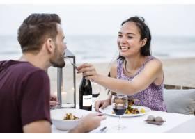 在海滩享受浪漫晚餐的情侣_3297364