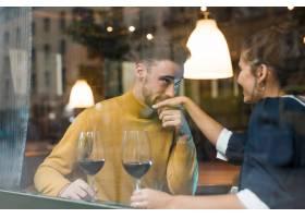 在餐厅里男人拿着酒杯亲吻快乐女人的手_3597224