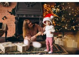 母亲带着女儿坐在圣诞树旁_3655521