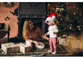 母亲带着女儿坐在圣诞树旁_3655522