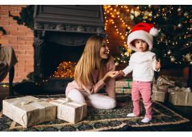 母亲带着女儿坐在圣诞树旁_3655523
