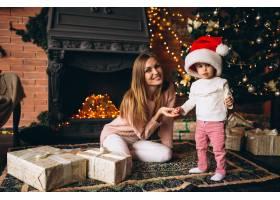 母亲带着女儿坐在圣诞树旁_3655524