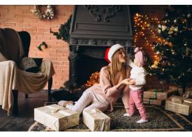 母亲带着女儿坐在圣诞树旁_3655525