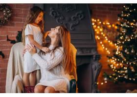 母亲带着女儿坐在圣诞树旁的椅子上_3654224