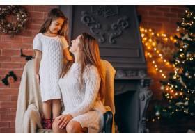 母亲带着女儿坐在圣诞树旁的椅子上_3654226