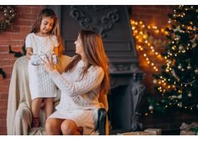 母亲带着女儿坐在圣诞树旁的椅子上_3654227
