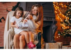 母亲带着女儿坐在圣诞树旁的椅子上_3654229