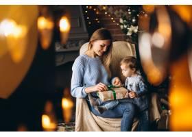 母亲带着女儿坐在圣诞树旁的椅子上_3655248
