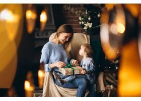 母亲带着女儿坐在圣诞树旁的椅子上_3655249
