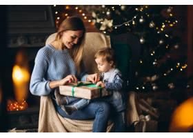 母亲带着女儿坐在圣诞树旁的椅子上_3655250