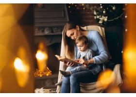 母亲带着女儿坐在圣诞树旁的椅子上_3655251