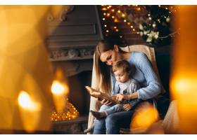 母亲带着女儿坐在圣诞树旁的椅子上_3655252