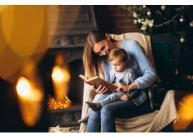 母亲带着女儿坐在圣诞树旁的椅子上_3655253