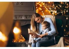 母亲带着女儿坐在圣诞树旁的椅子上_3655255