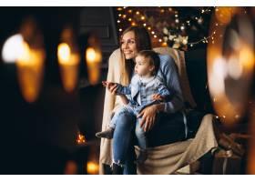 母亲带着女儿坐在圣诞树旁的椅子上_3655257