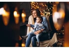 母亲带着女儿坐在圣诞树旁的椅子上_3655258