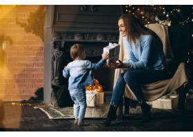 母亲带着女儿坐在圣诞树旁的椅子上_3655259