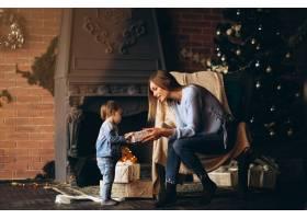 母亲带着女儿坐在圣诞树旁的椅子上_3655261