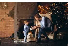母亲带着女儿坐在圣诞树旁的椅子上_3655262
