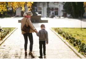 秋天母亲带着儿子在户外散步_3582196