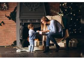 母亲带着女儿坐在圣诞树旁的椅子上_3655465