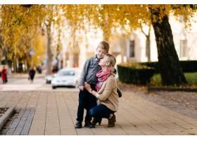 秋天母亲带着儿子在户外散步_3582197