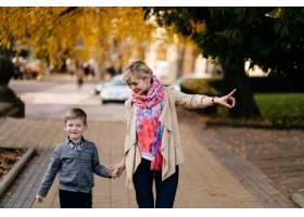 秋天母亲带着儿子在户外散步_3582198