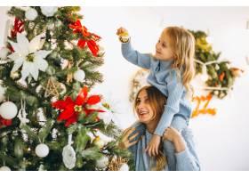 母亲带着女儿装饰圣诞树_3389605