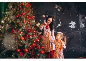 母亲带着女儿装饰圣诞树_3654131