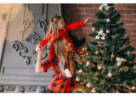 母亲带着女儿装饰圣诞树_3654257
