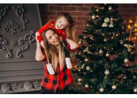母亲带着女儿装饰圣诞树_3654259