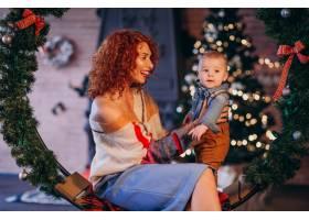 母亲带着她的小儿子在圣诞树旁_3654123