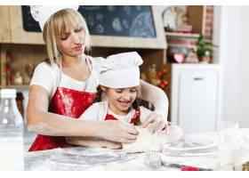 穿着相同衣服的妈妈和女儿在舒适的厨房里准_3342075